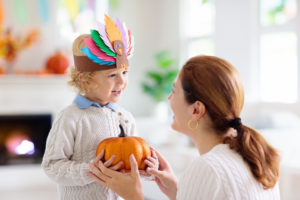child with a turkey hat holding pumpkin out to mom