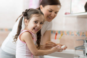 little girl washing hands with mom